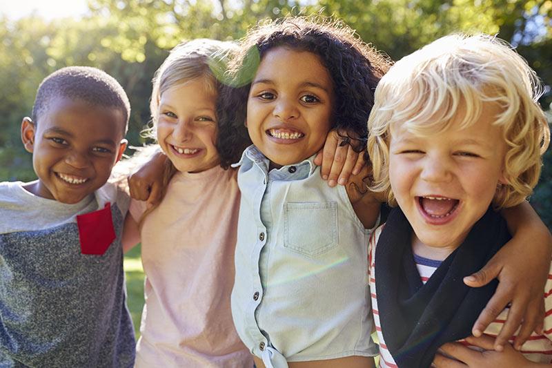 Lachende Kinder umarmen sich