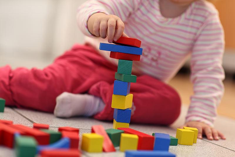 Kind sitzt auf dem Boden und spielt mit Buklötzern